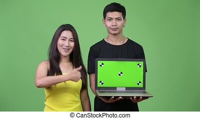 Young Asian couple showing laptop and giving thumbs up