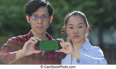Young Asian couple showing phone together outdoors