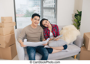 Young asian couple sitting on couch and looking at the blueprint of new home.