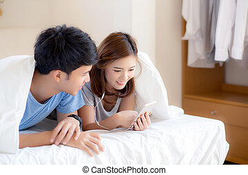 Young asian couple smile listen music with smart mobile phone on bed at bedroom with fun and enjoy, family sharing podcast or watching video from internet online with relax, lifestyle concept.