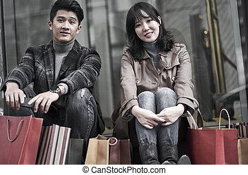 young asian couple taking a break while shopping in city