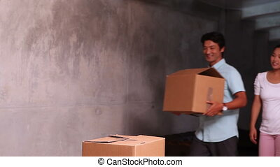Young asian couple unpacking moving boxes in their new home