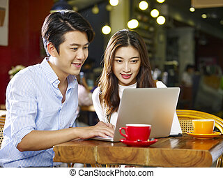 young asian couple using laptop in coffee shop