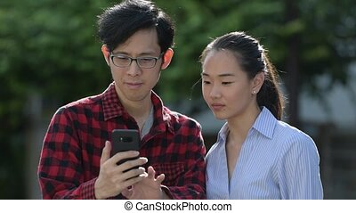 Young Asian couple using phone together outdoors