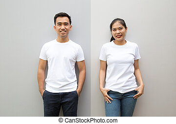 Young Asian couple wearing white t-shirt on grey color wall, Mock up template for design print concept