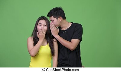 Young Asian couple whispering to each other - Studio shot of...