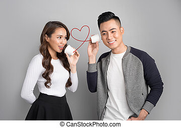 Young asian couple with can phone isolated on gray background