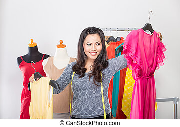 Young asian designer comparing two dresses in her hands, smiling