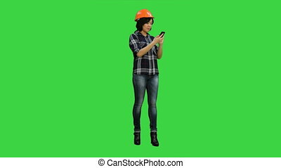 Young asian engineer use mobile phone on a Green Screen,...