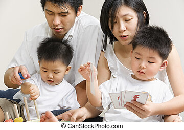 Young Asian family spending time together, teaching and ...