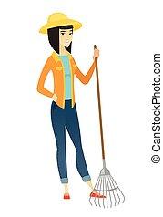 Young asian farmer holding gardening rake.