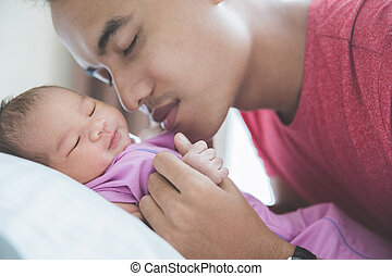 Young Asian father kissing his newborn sleeping baby, close eyes
