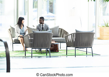 Young Asian female and African-american male executives speaking on bench