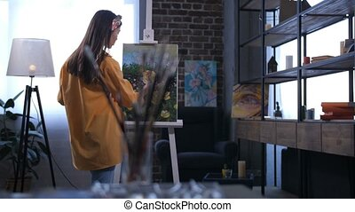 Young asian female artist creating a painting
