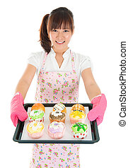 Young Asian female baking bread and cupcakes