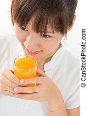Asian female drinking orange