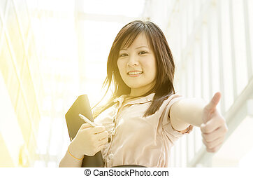 Young Asian female executive thumb up