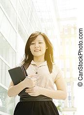 Young Asian female executive walking