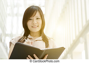 Young Asian female executive with diary