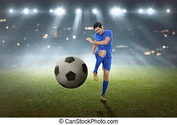 Young asian football player shooting the ball