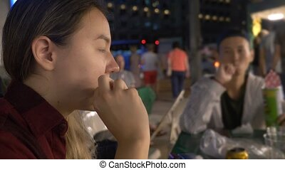 Young Asian girl eating street food at night outdoors. -...