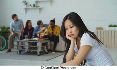 Young asian girl feels upset and isolated while her flatmates celebrating party at home