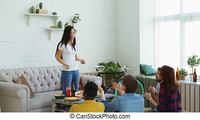 Young asian girl playing party game with her multi ethnic friends at home indoors