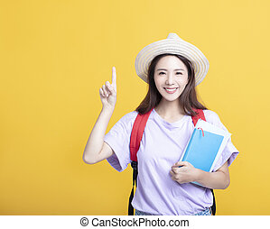 Young asian girl student holding book and pointing up