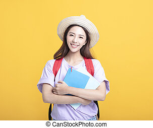 Young asian girl student holding book and smiling