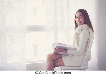 Young asian is holding reading book at home in morning.
