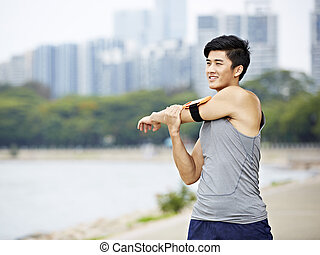 young asian jogger stretching arms before running