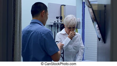 Young Asian male doctor examining a senior patient in the ...