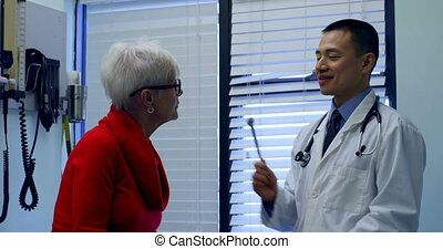 Young Asian male doctor examining a senior patient with ...