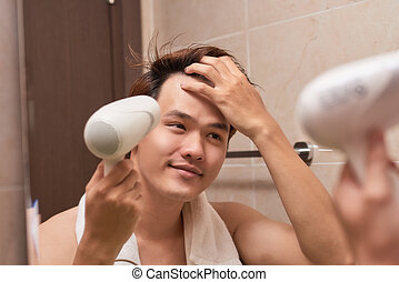 Young asian man blow drying hair in bathroom