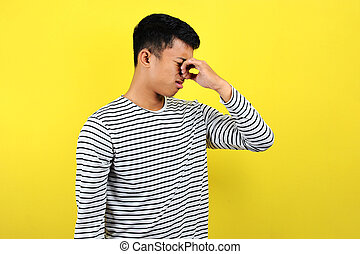 Young Asian man close his nose for bad smell, isolated on yellow