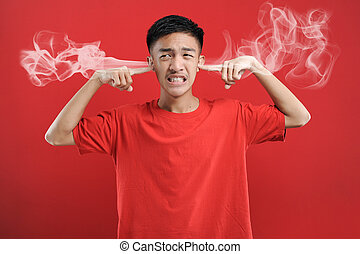 Young Asian man cover his ears with two fingers, fed up hearing hoax news