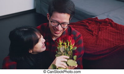 Young asian man giving red roses to his girlfriend. Happy valentines day. High quality 4k footage