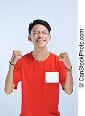 Young asian man happy and excited expressing winning gesture. Successful and celebrating