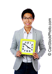 Young asian man holding a clock over white background