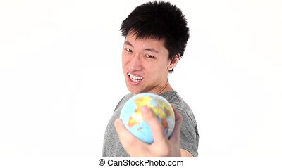 Young Asian man holding globe