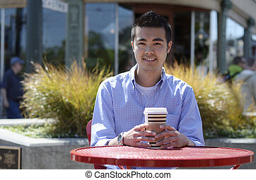 Young Asian man in a check shirt sitting outside with a hot drink