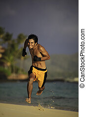 young asian man running on a  beach