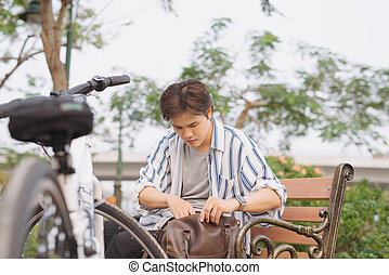 Young asian man searching items in his bag