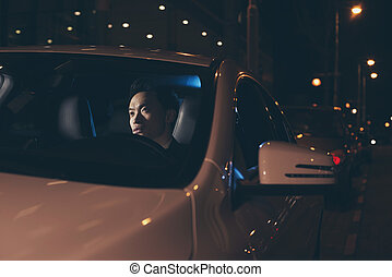 Young asian man sitting in car at night.