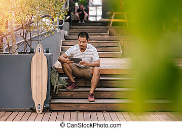 Young Asian man sitting on stairs outside using a tablet