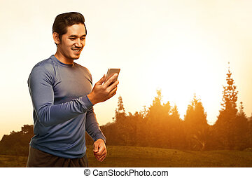 Young asian man standing in training clothes using his phone