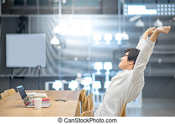 Young Asian man stretching out his arm in workspace