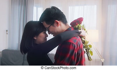 Young asian man surprising his girlfriend with a bouquet of red roses. High quality 4k footage