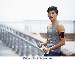young asian man taking a break during outdoor exercise