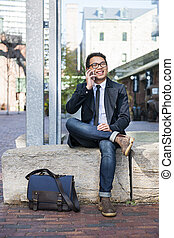 Young asian man talking on cellphone